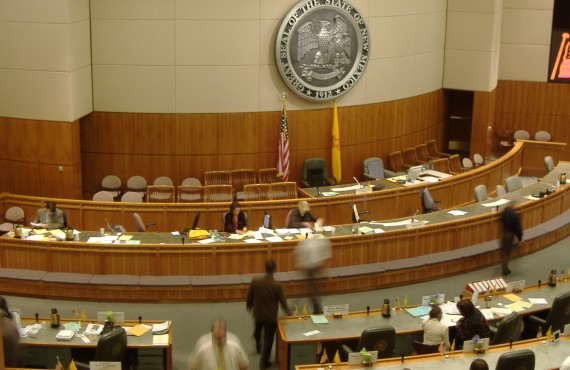 Interior view of NM State Senate chamber platform, with State Seal on the wall behind.