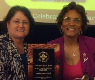 Con Alma Executive Director Dolores E. Roybal and former Board of Trustees Chair Pamelya Herndon display the award plaque.